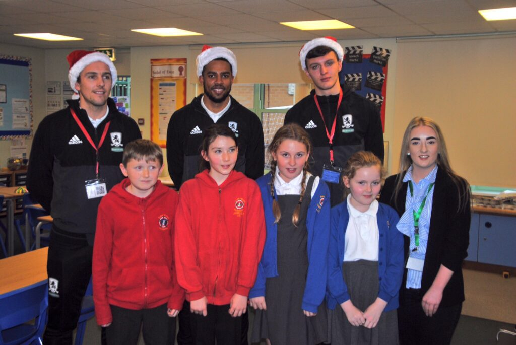 Stewart Downing, Cyrus Christie and Dael Fry pose for a photo with pupils from Rose Wood Academy