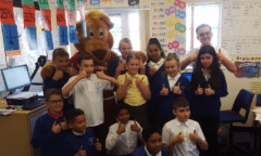 A class of children and Roary give their thumbs up