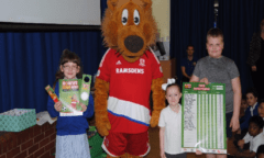 Roary poses alongside school children