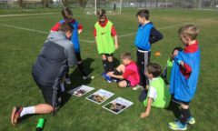 A coach teaches a school lesson outside on the football pitch