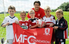 George Friend stood with children players in a football goal holding a flag