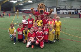 Roary the Lion posing with a group of children