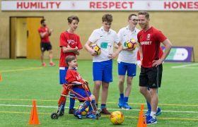 Adam Forshaw plays football with some children with disabilities