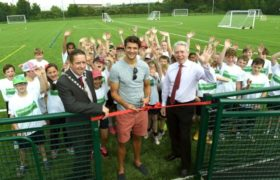 George Friend cuts a ribbon alongside a group of children to open the brand new Herlingshaw Centre 4G pitch