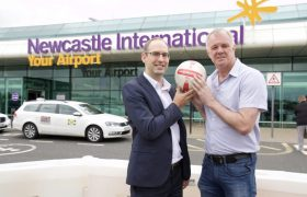 Gary Pallister holds a football with a director of Newcastle Airport