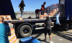 M F C Foundation staff and M F C staff unload bottles of orange from a lorry