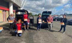 M F C Foundation staff with bottles of orange juice ready for delivery