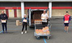 M F C Foundation staff help load orange juice onto a van