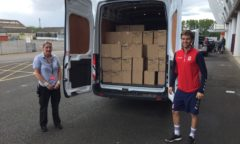 M F C Foundation's Ollie helps load a van with crisps